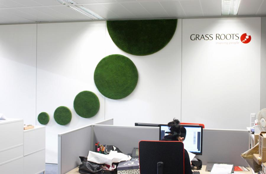 """Bildlogo aus Gras als Wandbegrünung in Büroraum des Unternehmens """"Grass Roots"""""""